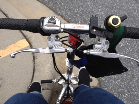 Photo has pavement in the background and shows the author's legs while sitting on a metallic scooter from a top-down view.